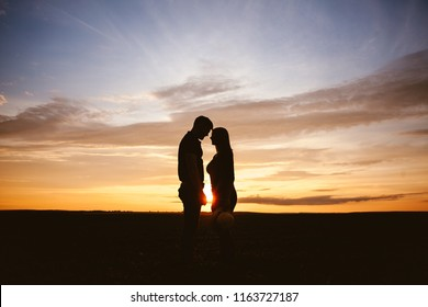 Silhouette of a guy and a girl.Couple in love at sunset