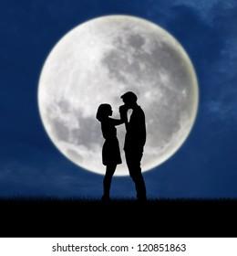 silhouette of guy kissing girl's hand on blue full moon background
