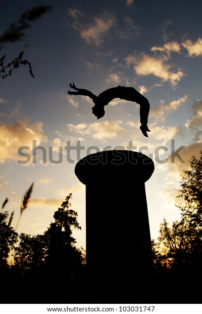 silhouette of gymnast jumping in sunset on tower