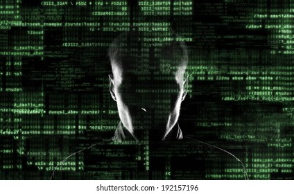 Silhouette of a hacker looking in camera with binary codes from monitor