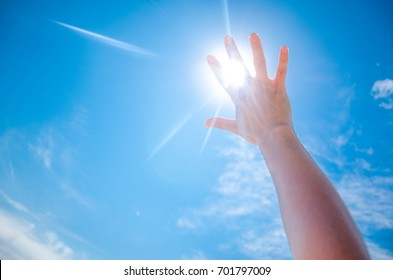 Silhouette of a Hand against a Sunset. Sun rays between fingers. Summer sunny day