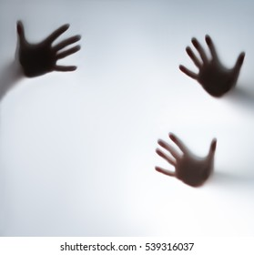 Silhouette of a hand behind the glass