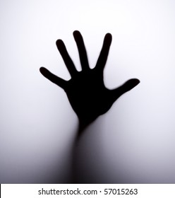 Silhouette of hand behind glass foreground