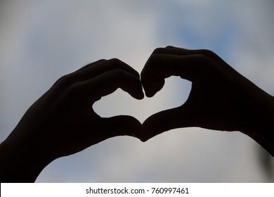 Silhouette hand in heart shape on blur sky background