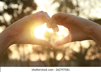 silhouette hand in heart shape with sunlight and flare