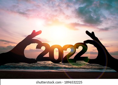 Silhouette hand holding 2022 year on beach side. Preparation happy new year to plan and starting new life and new business concept. - Shutterstock ID 1896532225