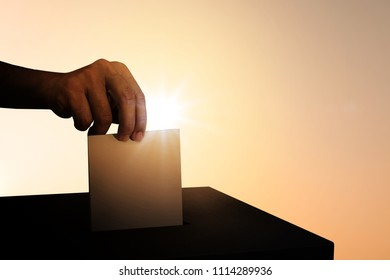 Silhouette of hand holding ballot at ballot box for voting concept.