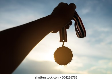 Silhouette of Hand holding gold medal on sky background . concept of victory
