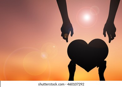 Silhouette hand holding heart shape sunset background. concept love
