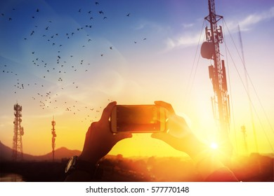 silhouette hand holding smartphone take photo at antenna and flare light