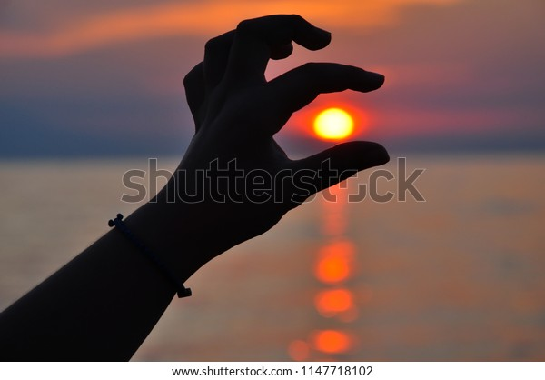 Silhouette of a hand holding the sun at sunset