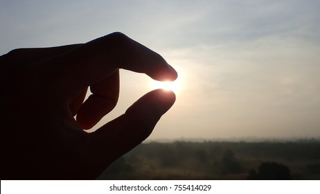Silhouette of a hand picking sunlight in the morning Success, dream and belief concept