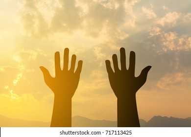 silhouette hand up praying with sunset light