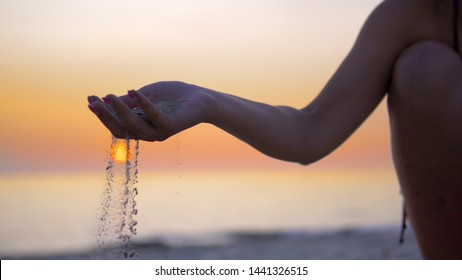 Silhouette hand releasing dropping sand. Sand flowing through the hands against orange ocean sunset. Summer beach holiday vacation concept
