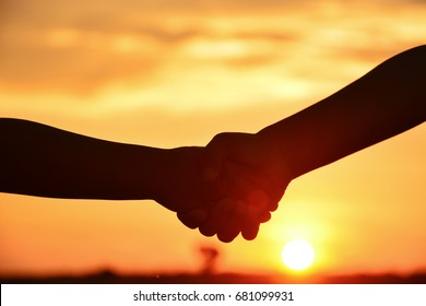 Silhouette of hand shake with sunset background.