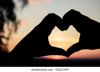 silhouette of a hand in the shape of a heart on a sunset background