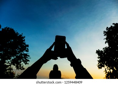 Silhouette of tourist's hand are taking photo by smartphone with beautiful nature background.