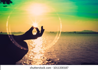 Silhouette, a hand of woman meditating in a Yoga pose or Lotus position at the Sea in Sunset and reflection of sunlight. Nature meditation and spa like zen or calm and solitude concept. Relax time.