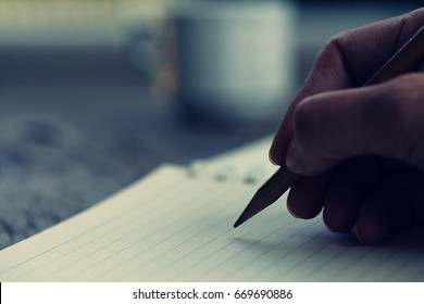 Silhouette of hand writing on paper closeup blur background. Closeup hand writing on paper in the morning dark color