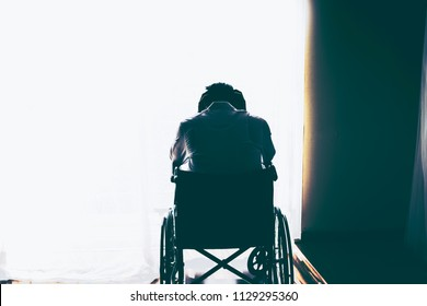 Silhouette of handicapped Man sitting on wheelchair in front of a large panoramic window in hospital,He is sad and lonely.