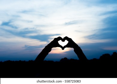 Silhouette  Hand-made heart-shaped over sunset background.