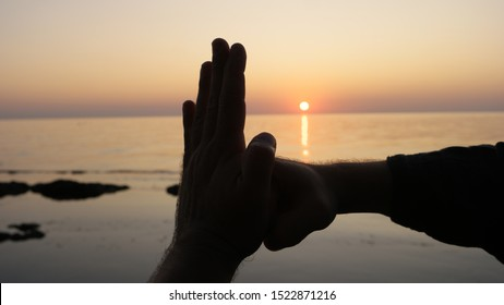Silhouette of the hands of a fighter Wing Chun on a background of sea sunset. chinese martial arts greeting