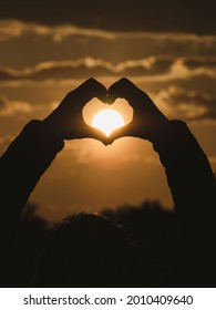 Silhouette of hands forming a heart at sunset
