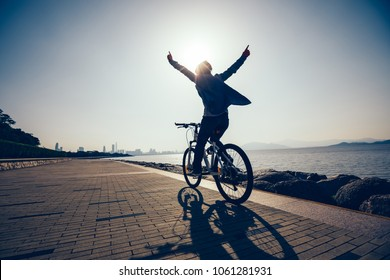 Silhouette of hands free cycling cyclist riding bike in the sunrise coast