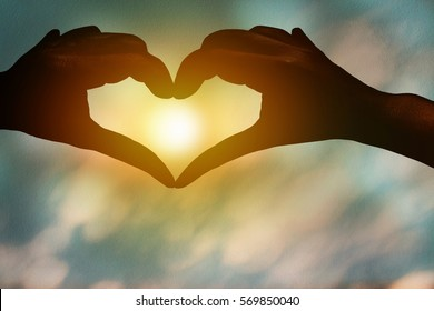 Silhouette hands heart with blurry sunset. Idea for good health of people.