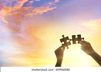 Silhouette of a hands holding a jigsaw puzzle piece at sky for teamwork concept