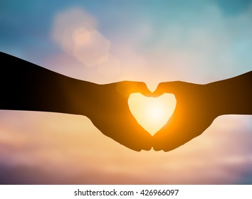 Silhouette hands making a heart shape