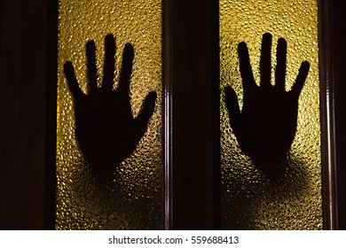 silhouette of hands outside the window