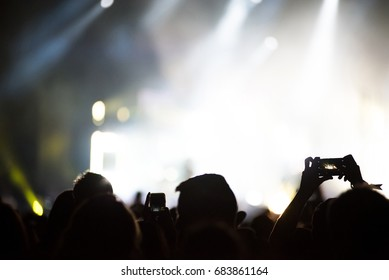 Silhouette of hands recording a concert with smart phones. Crowd of people using smart phones to photographing a concert