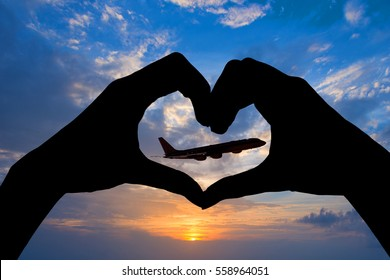 Silhouette of hands in the shape of a heart and airplane, sunset background
