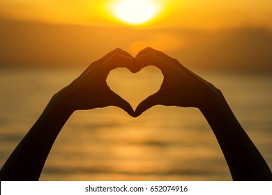 Silhouette Hands in shape of love heart at sunset.  Female hands in the form of heart against the sky pass sun beams.