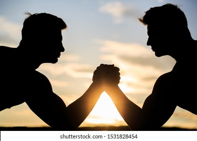 Silhouette of hands that compete in strength. Rivalry, closeup of male arm wrestling. Men measuring forces, arms. Two men arm wrestling. Rivalry, vs, challenge, strength comparison. Sunset, sunrise.
