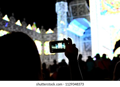 Silhouette of hands using camera phone to take pictures and videos at live concert, smartphone records live music festival.