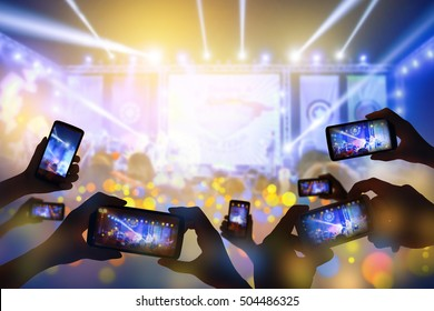 Silhouette of hands using smart phone to take pictures and videos at live concert  happy luxury party.