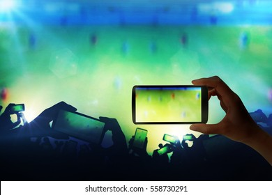 Silhouette of hands using smart phone to take pictures and videos at live football game