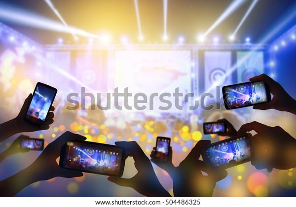 スマートフォンを使ってライブコンサートのハッピーラグジュアリーパーティーで写真やビデオを撮る手のシルエット。