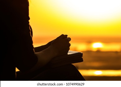 silhouette of the hands of a young woman praying to God in the nature, the girl holds her hands on the Bible near the tree at sunset, the concept of religion and spirituality