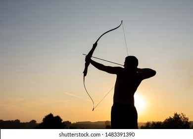 Silhouette of a handsome man with an ancient weapon bow and arrow on a background of sky and sunset