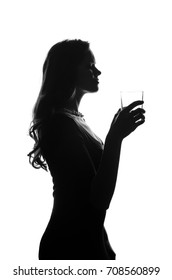 Silhouette of handsome woman with long hair with glass in her hand. She stays side to camera and looks stright. Cut-out scene. Studio shot