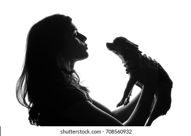 Silhouette of handsome woman standing with smal dog in her hands. She lifted pet over the head and looks on it with smile. Girl wants to kiss puppy. Cut-out scene. Studio shot