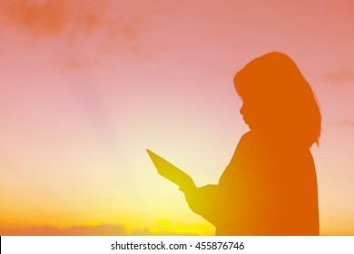 Silhouette of happy asian young girl using digital tablet over beautiful twilight sunset.