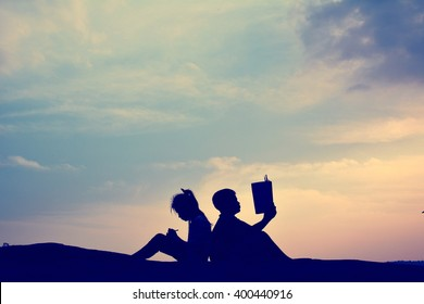 Silhouette of happy boy and girl reading a book in the sky sunset ,free time on holiday