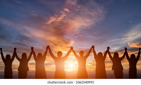 Silhouette of happy business human team making high hands over head in sunset sky evening time background for business teamwork concept and freedom