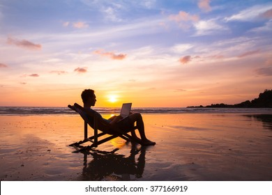 silhouette of happy business man with laptop working on the beach