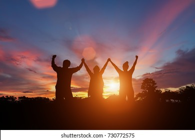 Silhouette of happy business people making high hands in sunset sky background for business teamwork concept