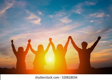 Silhueta de equipe de negócios feliz fazendo mãos altas no fundo do céu do sol para o conceito de trabalho em equipe de negócios